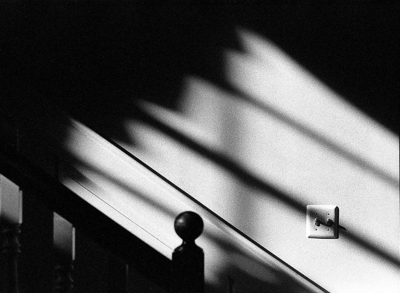 Light Switch Stairs Banister Shadows black and white film photography